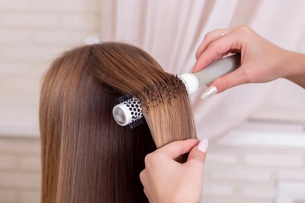 Die hände des friseurs bürsten langes brünettes haar