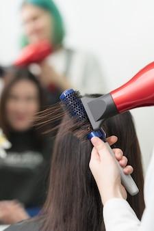 Die hände des friseurs trocknen brünette haare des kunden mit rotem haartrockner und blauem kamm im professionellen schönheitssalon.