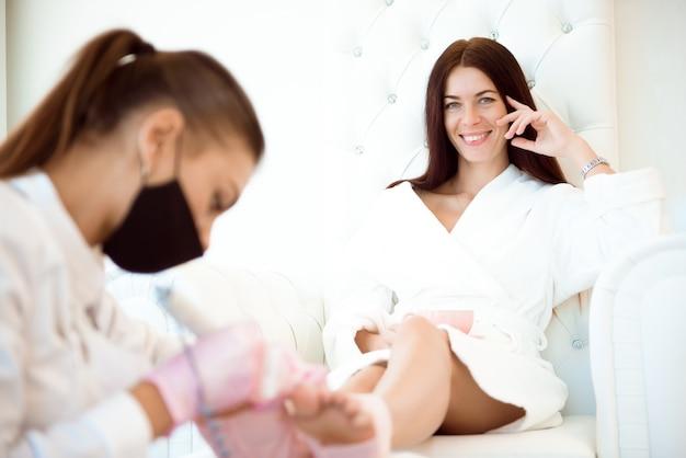 Die hände des fußpflegers tragen gummihandschuhe und tragen nagellack auf die zehennägel auf.