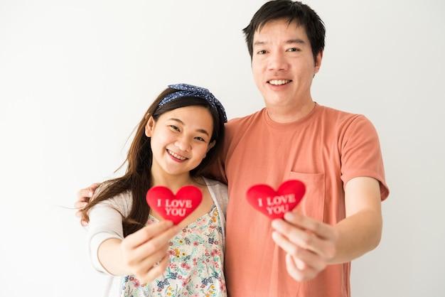 Die hände des glücklichen lächelnden jungen asiatischen paares, das rotes falsches herz mit ich liebe sie text mit kopienraum auf weißem hintergrund hält. 2021 valentinstagfeier.