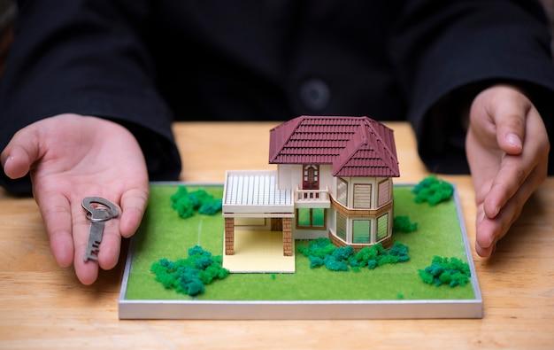 Die hände des hausverkäufers präsentieren das musterhaus