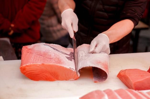 Die hände des japanischen chefs, der chefmesser verwendet, schnitten stück frische thunfische für verkauf an kunden im morgenfischmarkt, japan.