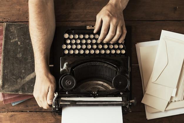 Die hände des jungen mannes, die auf einer antiken weinlese-schreibmaschine tippen