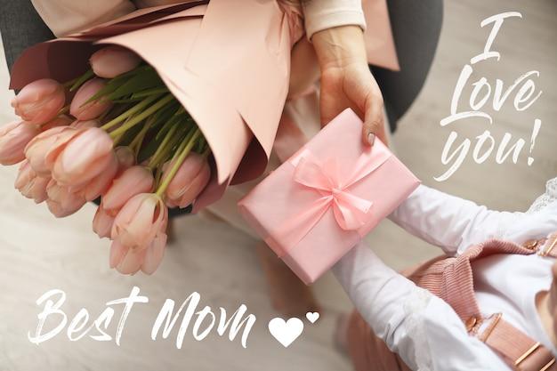 Die hände des kindes halten eine schöne rosa geschenkbox mit band und rosa tulpenblume. ansicht von oben, nahaufnahme. vorbereitung auf die feiertage.