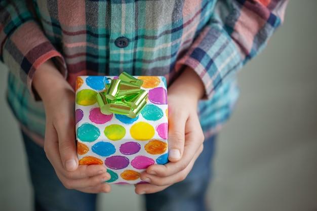 Die hände des kindes halten feiertag verzierte bunte geschenkbox