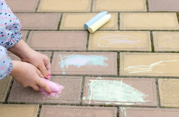 Die hände des kleinen mädchens zeichnen auf asphalt und pflastern steine mit bunter kreide. kinder spielen im freien