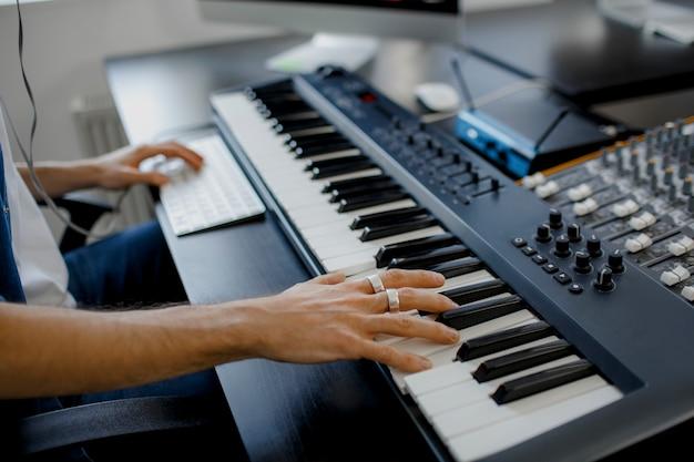Die hände des komponisten auf den klaviertasten im tonstudio
