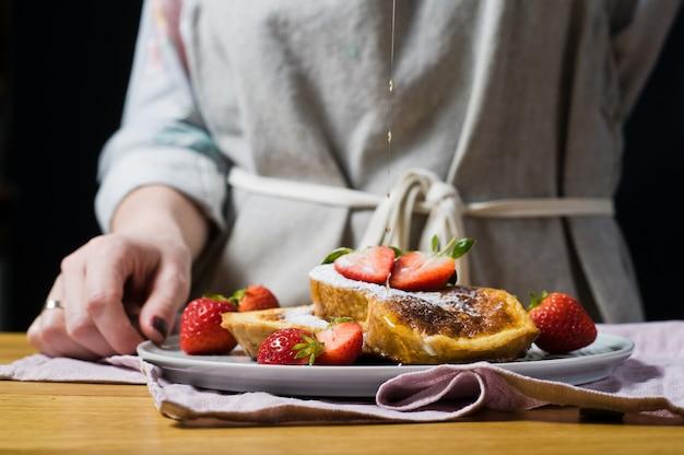 Die hände des küchenchefs gossen ahornsirup auf french toast.