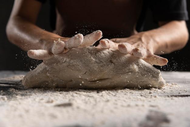 Die hände des küchenchefs kneten den teig mit mehl