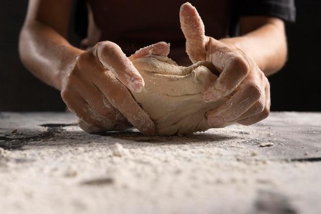 Die hände des küchenchefs kneten teig mit mehl auf dem tisch