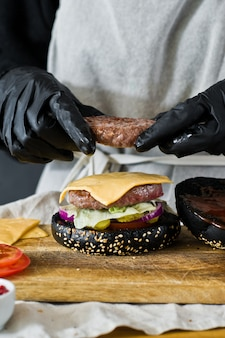 Die hände des küchenchefs kochen den burger. das konzept des kochens des schwarzen cheeseburgers. selbst gemachtes hamburgerrezept.