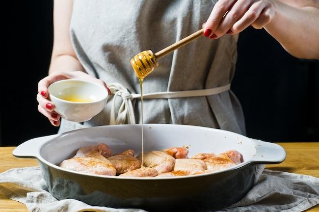 Die hände des küchenchefs marinieren rohe hühnerflügel in honig.
