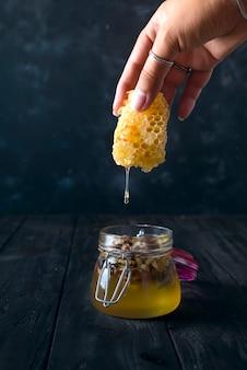 Die hände des mädchens halten ein stück wabe, aus der der honig in das glas fließt.