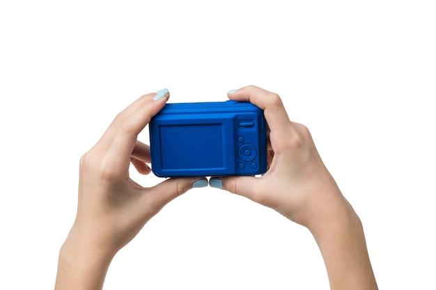Die hände des mädchens halten eine blaue kamera, die auf einem weißen isoliert ist. ausrüstung zum schießen.
