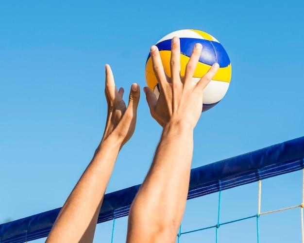 Die hände des mannes bereiten sich darauf vor, den ankommenden volleyball über das netz zu schlagen