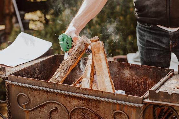 Die hände des mannes brennen beim grillen mit brennholz durch gasbrenner auf dem hinterhof. picknick-konzept. der fokus liegt auf wald.