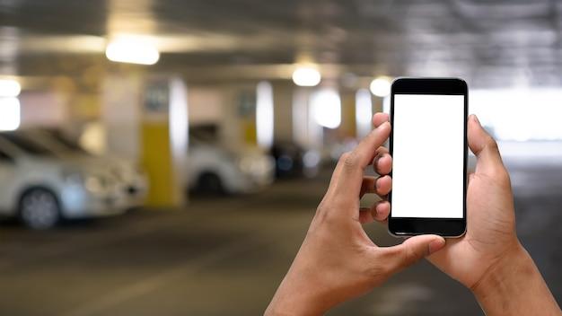 Die hände des mannes, die leeren bildschirm des smartphone im autoparken halten.