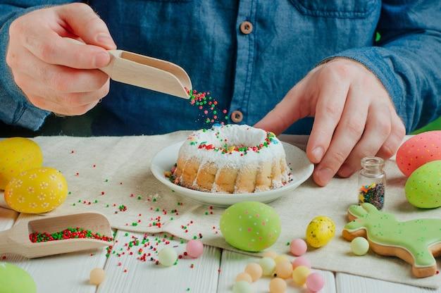 Die hände des mannes, die ostern-kuchen mit zucker verzieren, besprüht in der bewegung