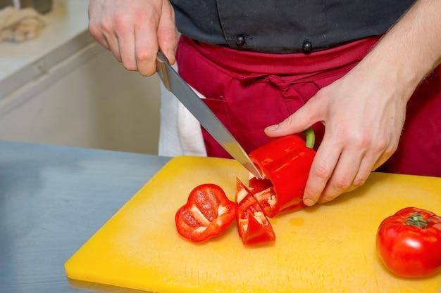 Die hände des mannes, die reife tomate in scheiben auf einer tabelle schneiden. mann in der küche bereitet einen salat zu. hand, die eine frische gartentomate mit großem küchenmesser schneidet