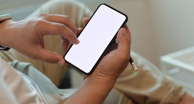 Die hände des mannes, die smartphone des leeren bildschirms halten