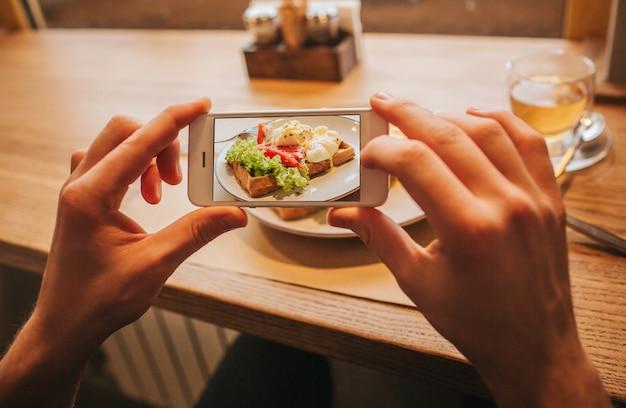 Die hände des mannes hält telefon und macht foto der geschmackvollen mahlzeit auf platte. es ist bunt und lecker.