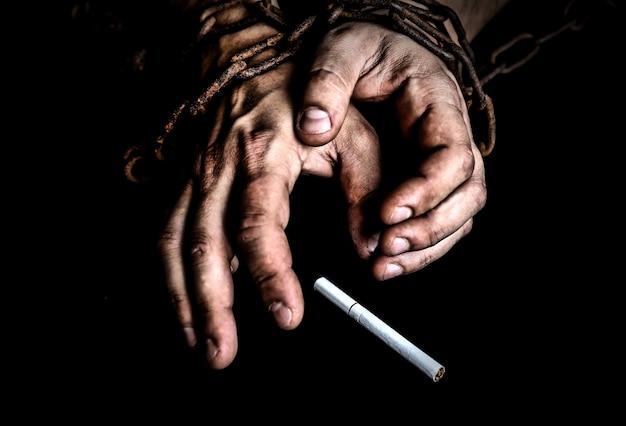 Die hände des mannes in alten rostigen ketten nahe der zigarette. süchtig nach rauchen. gefährliche gewohnheit.