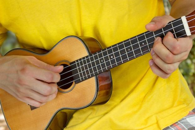 Die hände des mannes spielen ukulele