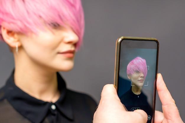 Die hände des mannfriseurs fotografieren auf dem smartphone ihre kurze rosa frisur des kunden.