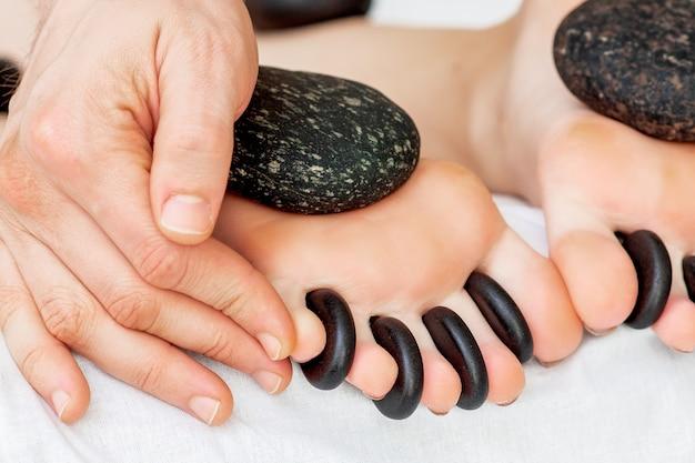 Die hände des massagetherapeuten legen steine zwischen die zehen der frau, während die steinmassage an den füßen aus nächster nähe ist.