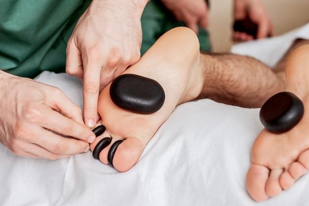 Die hände des massagetherapeuten legen steine zwischen die zehen des menschen, während die steinmassage an den füßen ganz nah ist.