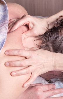 Die hände des masseurs massieren den kragenbereich des rückens des patienten.