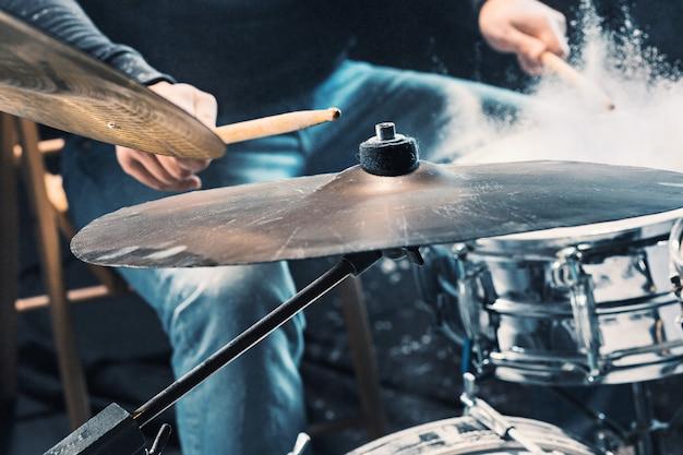 Die hände des schlagzeugers, der vor dem rockkonzert am schlagzeug probt. mann, der musik auf schlagzeug im studio mit showeffekt in form von mehl aufnimmt