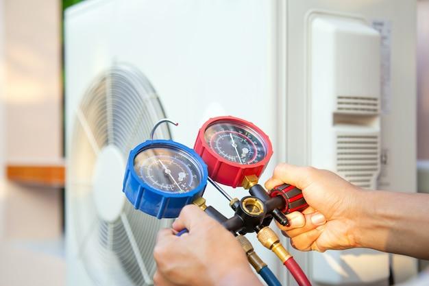 Die hände des technikers verwenden ein messwerkzeug, um die klimaanlage zu überprüfen.