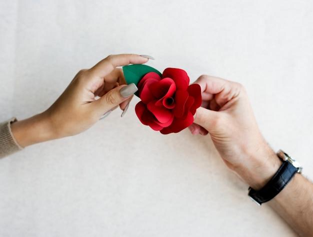 Die hände, die ein papier halten, stellten rotrose her