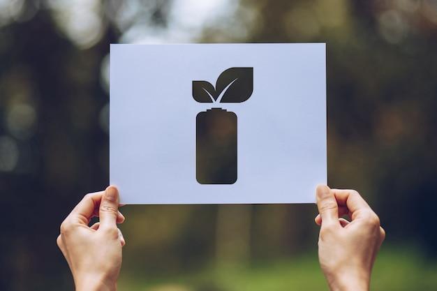 Die hände, die herausgeschnittenes papier halten, verlässt batteriesparende energievertretung
