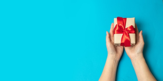 Die hände, die kraftpapier halten, wickelten präsentkarton im paket mit rotem band ein