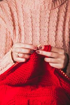 Die hände, die nadeln halten und eine rote warme jacke stricken