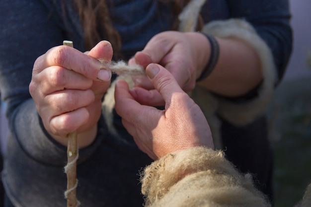 Die hände, die wollvlies von hand spinnen