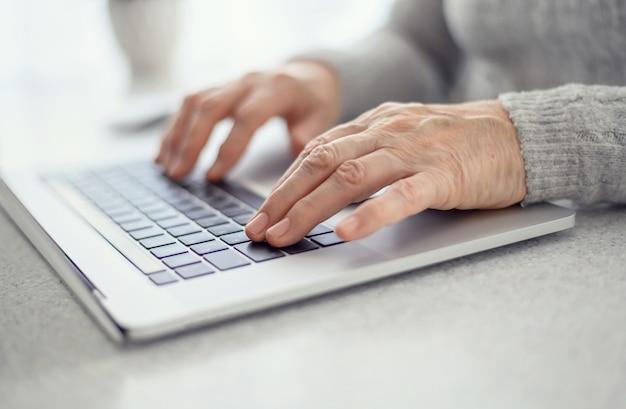 Die hände einer älteren frau arbeiten an einer laptop-nahaufnahme unter verwendung moderner technologie im täglichen leben.