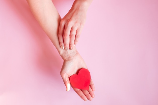Die hände einer dame, die ein herz auf einer rosa wand, valentinstag hält