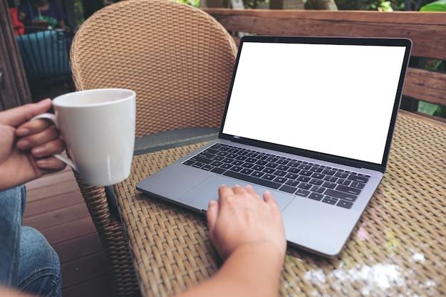 Die hände einer frau, die laptop mit leerem weißen desktop-bildschirm beim trinken von heißem kaffee auf holztisch im café verwendet