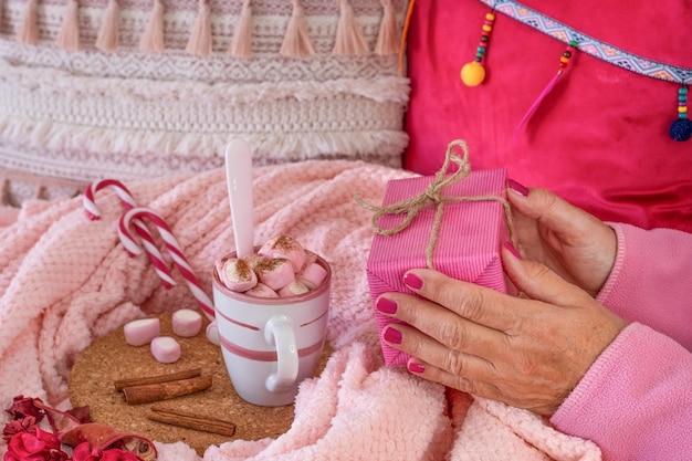 Die hände einer frau im rosafarbenen schlafanzug, die ein geschenkpaket hält, neben ihr eine tasse mit heißem kakao mit marshmallows und zimtpulver. weihnachtsferien und glückliches menschenkonzept