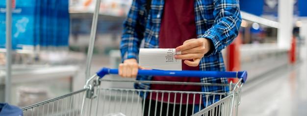 Die hände einer person, die ein papierblatt mit einer einkaufsliste halten und den kauf von produkten im lebensmittelgeschäft überprüfen