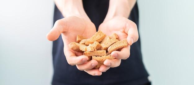 Die hände einer person, die kalorienarmen gesunden zwieback halten, passen diät