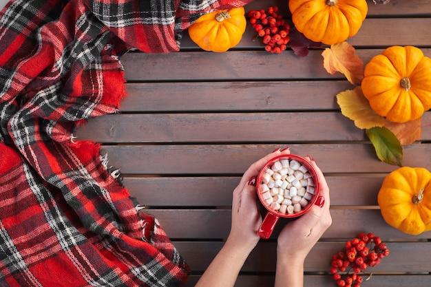 Die hände einer schönen frau, die roten becher mit kakao und marshmallows hält herbststimmung wärmendes getränk gemütliche atmosphäre