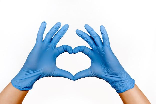 Die hände eines arztes oder einer krankenschwester in medizinischen handschuhen zeigen ein herz auf einem weißen hintergrund, einen fürsorglichen arzt und ein medizinkonzept