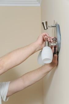 Die hände eines elektrikers zünden eine wandlampe mit led-lampe an
