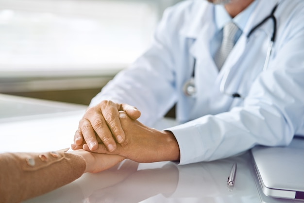 Die hände eines freundlichen männlichen arztes halten die hand der patientin für ermutigung und empathie. konzept für partnerschaft, vertrauen und medizinische ethik. verminderung und unterstützung von schlechten nachrichten. patientenjubel und unterstützung