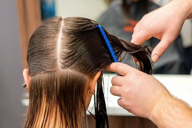 Die hände eines friseurs, der die haare einer jungen frau kämmt, trennten sich im friseursalon abschnittsweise