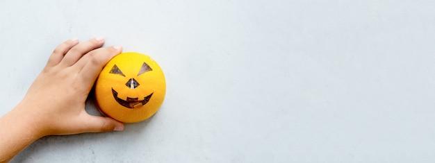Die hände eines jungen, der für den halloween-feiertag eine gruselige schnauze auf einen kürbis zeichnet. minimalismus. grau und orange.